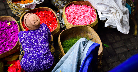 Old woman selling colorful flower in the traditional open market for praying and gift ceremony