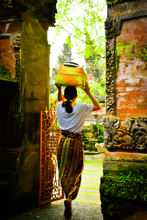 Local Balinese woman wearing traditional uniform entering a sacred temple with offering gift for ritual festival event
