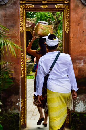 Local family with traditional uniforms entering a sacred temple to pray, worship and celebrate religious social gathering festival