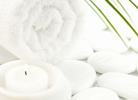 White pebbles, candle, towel and palm leaf over white. Selective focus.