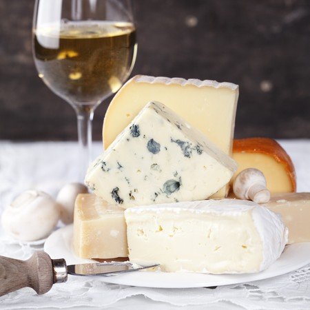 White wine and Various types of cheese on a plate