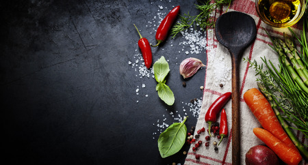 Wooden spoon and ingredients on dark background.