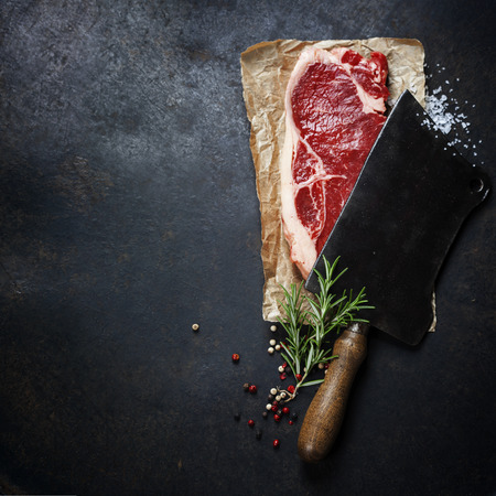 vintage cleaver and raw beef steak on dark background