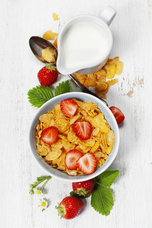 Healthy Breakfast with corn flakes, milk and strawberry on old wooden background. Health and diet concept
