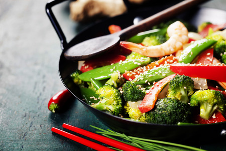 Chinese cuisine. Colorful stir fry in a wok. Shrimps with vegetables