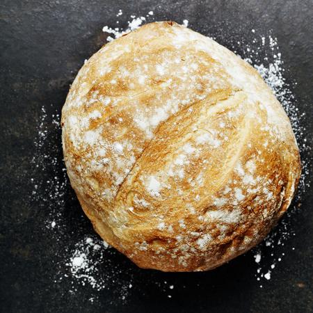 Homemade bread loaf on rustic dark background