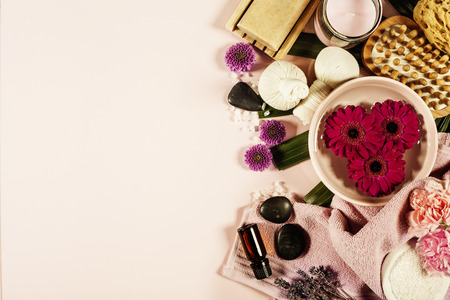 Spa background with sea salt, bowl ,flowers, water, soap bar, candles, essential oils, massage brush and flowers,top view. Flat lay. Pink backgroundの写真素材