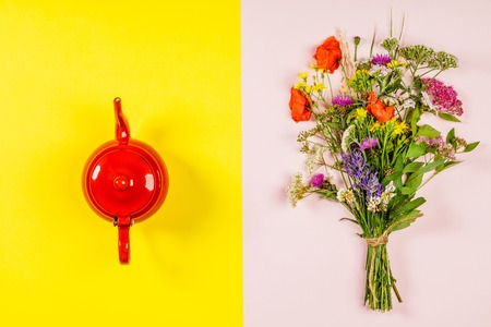 Wild flower bouquet and teapot, flat lay, top view. Herbal tea and healthy food concept