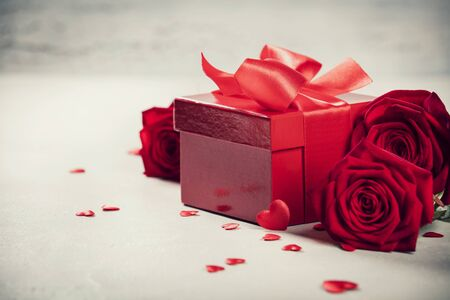 Photo pour Valentines Day concept. Valentines gift boxes tied with a red satin ribbon bow and beautiful roses on rustic background. - image libre de droit