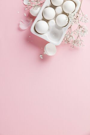 Photo for White eggs in white ceramic holder and flowers on pink - Royalty Free Image
