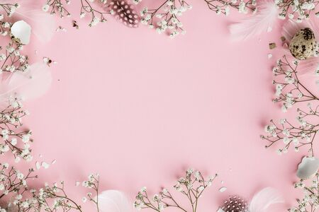Photo for Happy Easter frame with flowers, feathers and egg shells on pink - Royalty Free Image