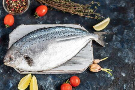 Photo pour Sea tasty fresh fish on a dark background. Frozen product. Fish with aromatic herbs, spices and vegetables - the concept of a healthy diet, diet or cooking. Copy space - image libre de droit