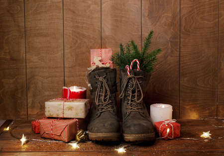 Photo for Christmas shoes on a wooden background around gifts, burning candles, green fir branches. Christmas still life. - Royalty Free Image