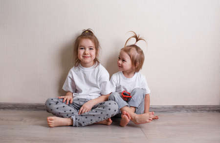 Photo pour two little girls are sitting on the floor near the wall in the house. - image libre de droit