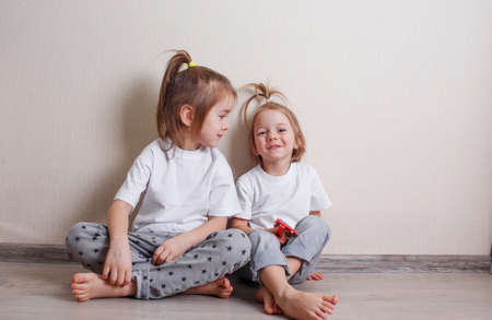 Photo pour two little girls sit at home on the floor near the wall and laugh merrily. - image libre de droit