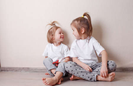 Photo pour two little girls sit at home on the floor near the wall and play fun with each other. A fun and carefree childhood. - image libre de droit