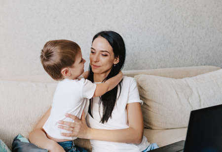 Photo pour happy mom hugs her young son while sitting on the couch in front of her laptop - image libre de droit