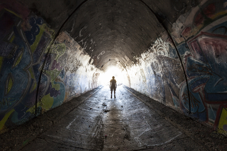 Simi Valley California - August 1, 2015:  Man exploring graffiti covered tunnel under the 10 lane 118 freeway near Los Angeles.