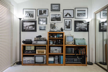 Foto de Bric-a-brac shelves wth collectable vintage electronics and framed black and white photos in small home office.   Wall art is the photographers work. - Imagen libre de derechos