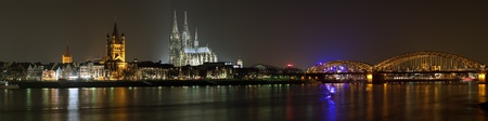 Night panorama of Cologne with Great St  Martin Church, Cologne Cathedral and Hohenzollern Bridge from bank of the Rhine river, Germany
