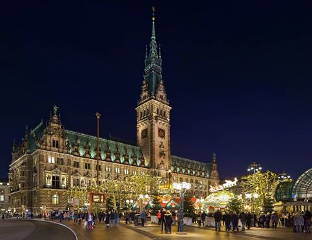 Foto de HAMBURG, GERMANY - DECEMBER 5, 2018: Christmas market at Town Hall square in front of Hamburg Town Hall in dusk. This is the most popular and most visited Christmas market of the city. - Imagen libre de derechos