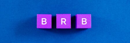 Foto de Top view image of BRB abbreviation spelled on violet colored wooden dices. Over  blue background. - Imagen libre de derechos