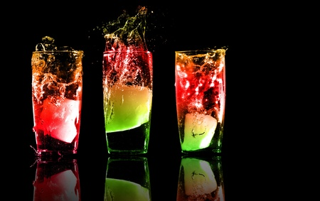 Three exotic tropical cocktails with reflections on a white background