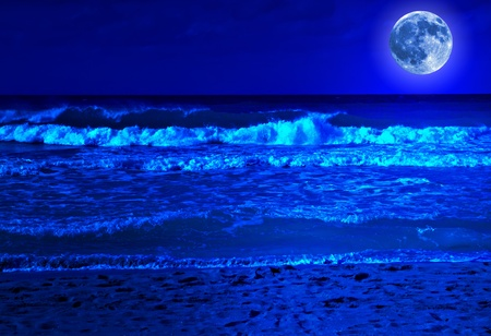 Stormy beach at midnight with a bright full moon