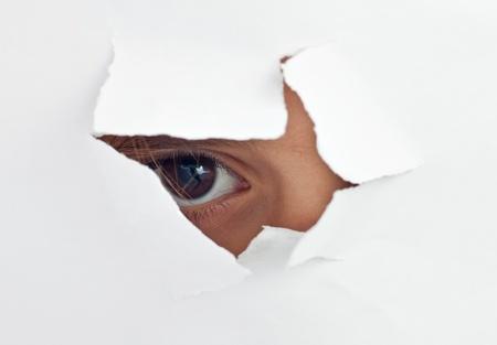 Photo pour An eye peeking through a hole in a white paper sheet - image libre de droit