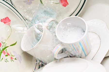 Washing dirty glasses and dishes with detergent and water