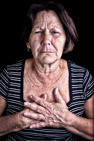 Mature woman suffering from chest pain or depression on a black background