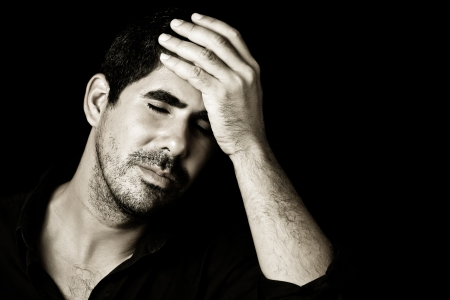 Monochromatic image of a young handsome hispanic man worried or having a headache isolated on black