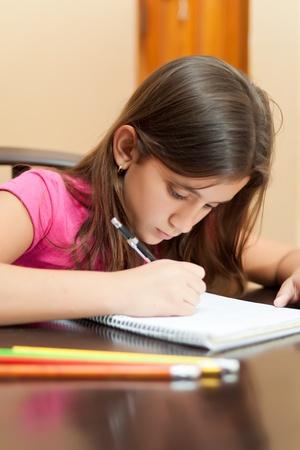 Portrait of a cute hispanic girl working on her school homework