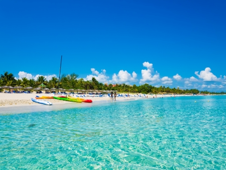 The beautiful beach of Varadero in Cuba with colorful boats and thatched umbrellas  image taken from the sea