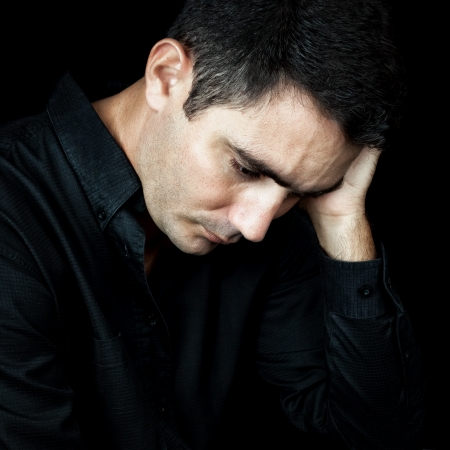 Dramatic close-up of a worried and depressed man isolated on black