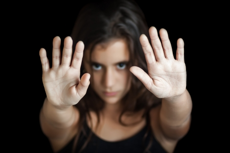 Hispanic girl with her hand extended signaling to stop useful to campaign against violence, gender or sexual discrimination  Focused on her hand