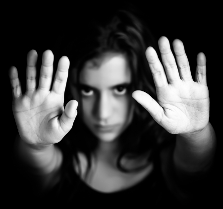 Black and white image of a girl with her hand extended signaling to stop useful to campaign against violence, gender or sexual discrimination  image focused on her hands