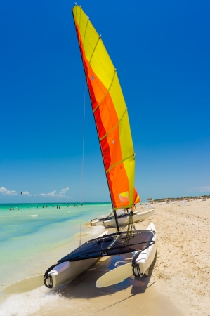 Catamaran with its open colorful sail on the shore of Varadero beach in Cuba