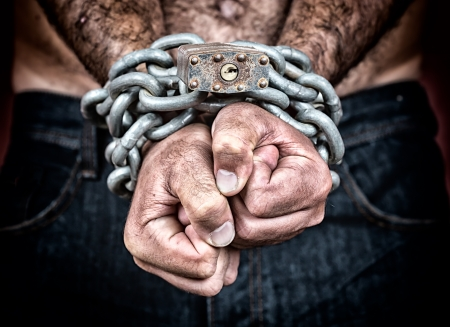 Dramatic detail of the chained hands of an adult man  with a strong chain and padlock