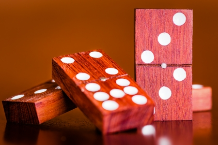 Tiles from a game of dominoes on a wooden table with a diffused background