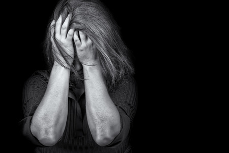 Black and white image of a young woman crying useful to illustrate stress, depression or domestic violence