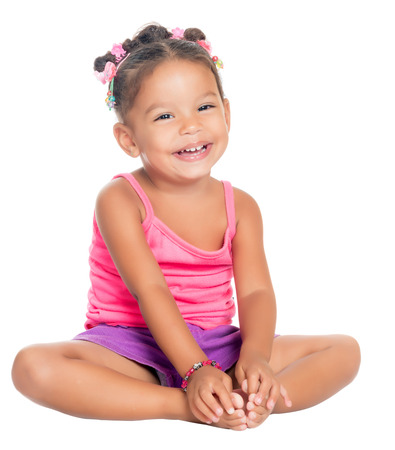 Multiracial small girl laughing sitting on the floor  isolated on white