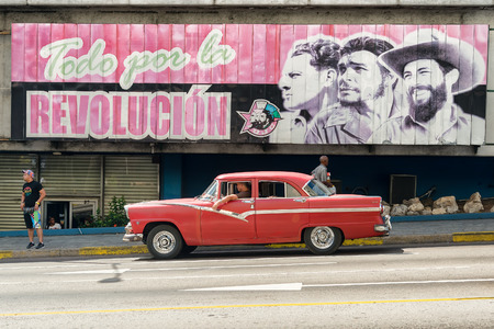Vintage american car next to a poster supporting the Cuban Revolution