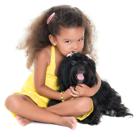 Cute small girl kissing her pet dog isolated on white