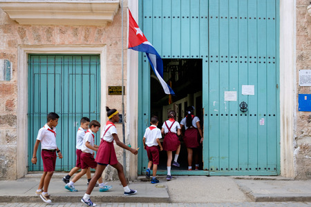 A group of uniformed cuban children entering a primary school in Old Havana