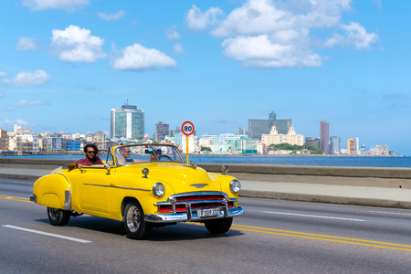Photo pour Old convertible car on the Havana malecon avenue with a view of the sea and the city skyline - image libre de droit
