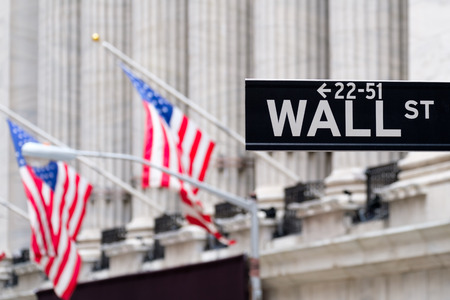 Foto de Wall street sign with the New York Stock Exchange and american flags on the background - Imagen libre de derechos