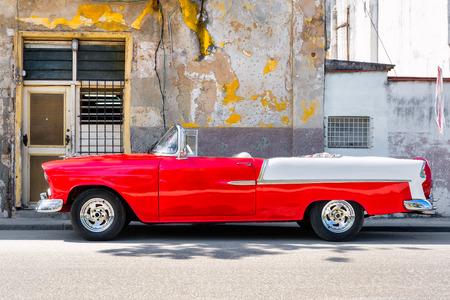 Photo pour Classic red convertible car next to a shabby building in Old Havana - image libre de droit