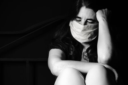 Photo pour Stressed and sad woman wearing a face mask to avoid respratory diseases - Black and white portrait sitting on a bed - image libre de droit