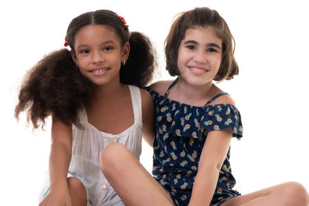 Photo pour Two friendly small girls, friends or sisters  - Hispanic and african-american - Isolated on white - image libre de droit